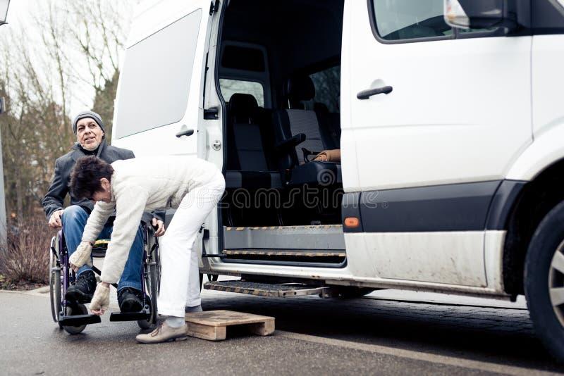 Nurse Helping Senior Man Exit A Van. Nurse helping senior men exit a van and get to his wheelchair royalty free stock image