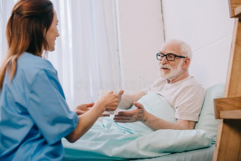 Nurse helping senior patient in bed to hold stock photo
