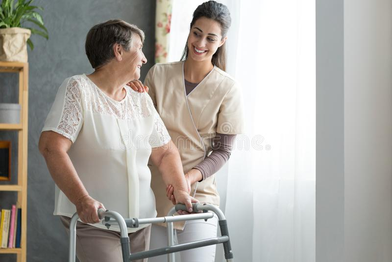 Nurse helping senior to walk stock photo