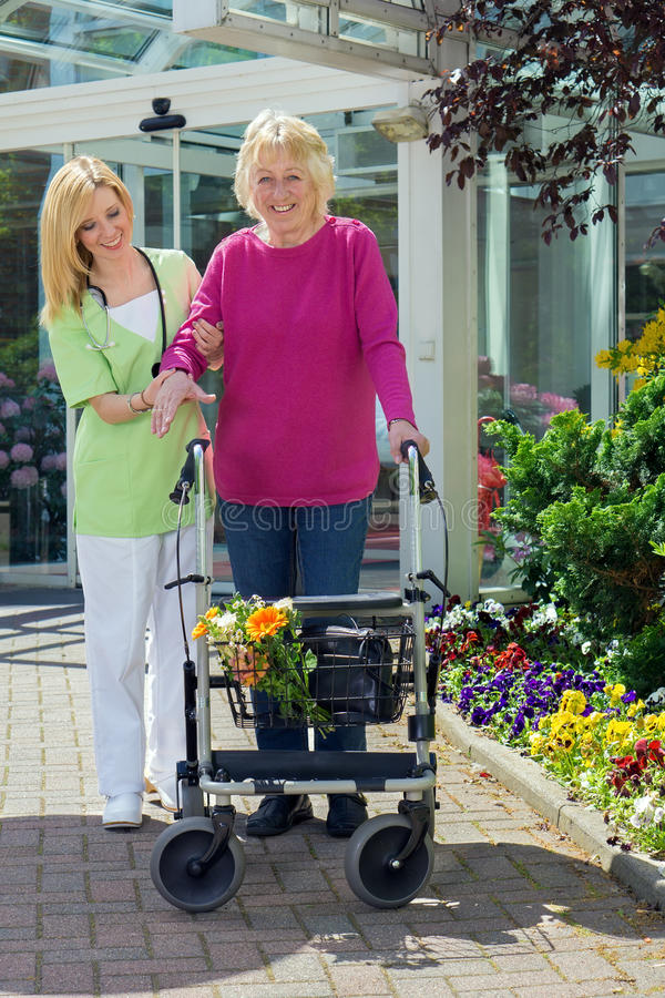 Nurse Helping Senior Woman to Walk with Walker royalty free stock image