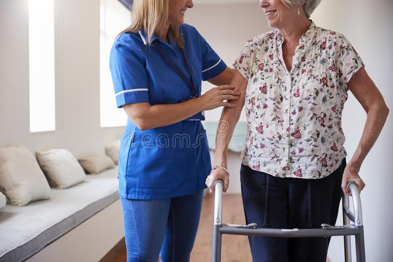 Nurse helping senior woman use a walking frame, mid section royalty free stock images