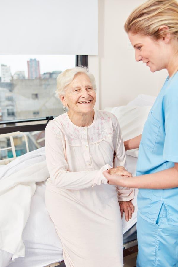 Nursing lady helps senior woman to get up royalty free stock image