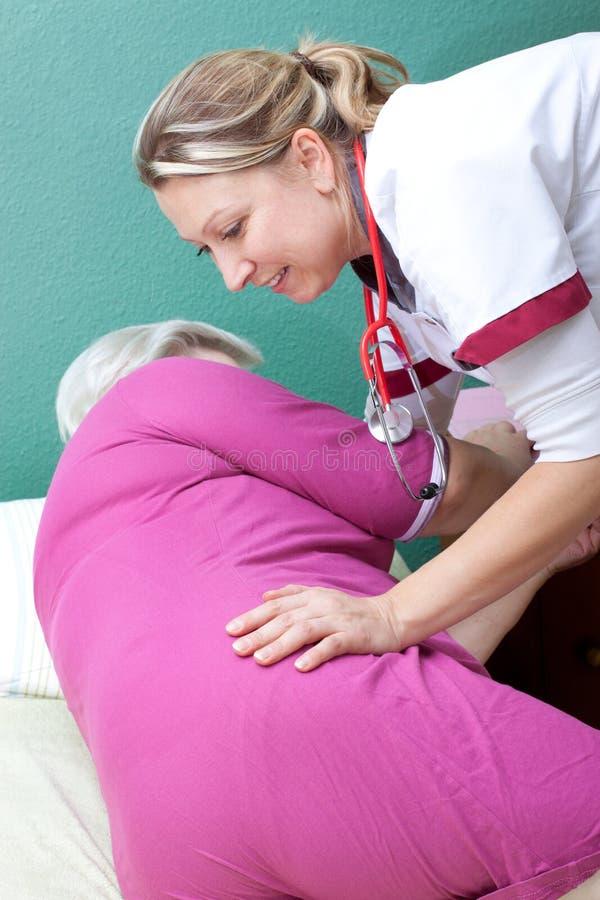 Nurse helps patient to get up stock images