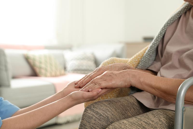 Nurse holding elderly woman`s hands indoors, space for text. Assisting senior people stock photography