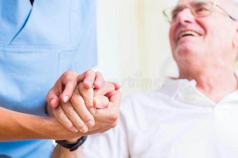 Nurse holding hand of senior man in rest home royalty free stock photos