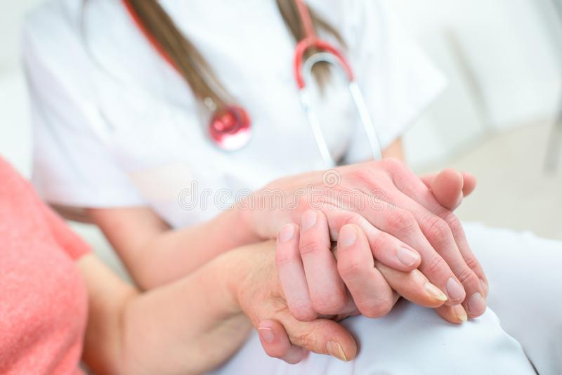 Nurse holding hand senior woman in wheel chair stock images