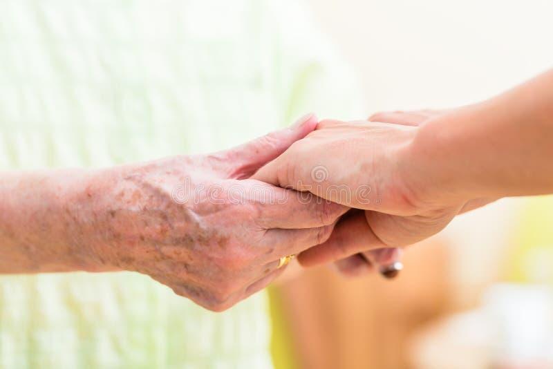 Nurse holding hands of senior woman royalty free stock image