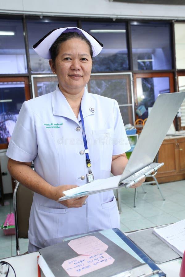 Nurse holding patient profile chart on ward. UBON RATCHATHANI, THAILAND – AUG 21, 2013 : Unidentified nurse holding patient profile chart on ward on Aug royalty free stock photos