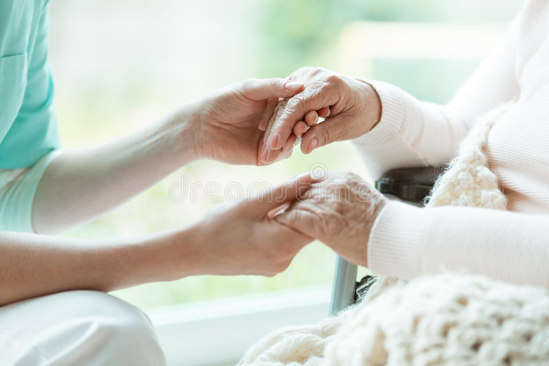 Nurse holding patient`s hands stock photos