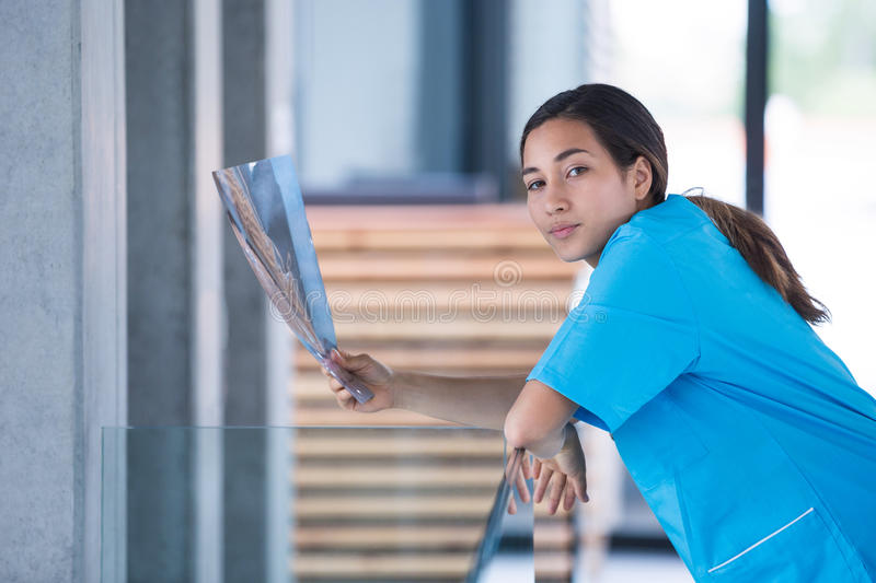 Nurse holding a X-ray report. Portrait of a nurse holding X-ray report in hospital royalty free stock images