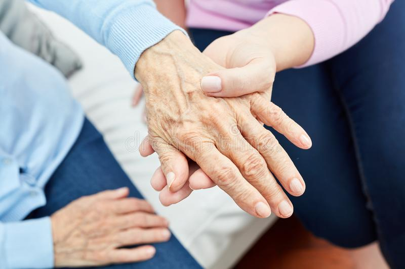 Nurse holds the hand of a senior citizen royalty free stock photo