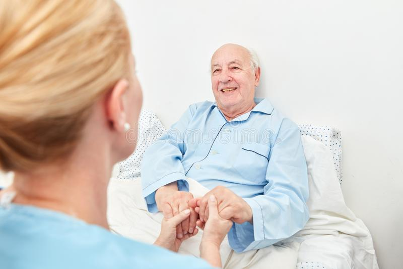 Nurse holds the hands of a sick patient royalty free stock image