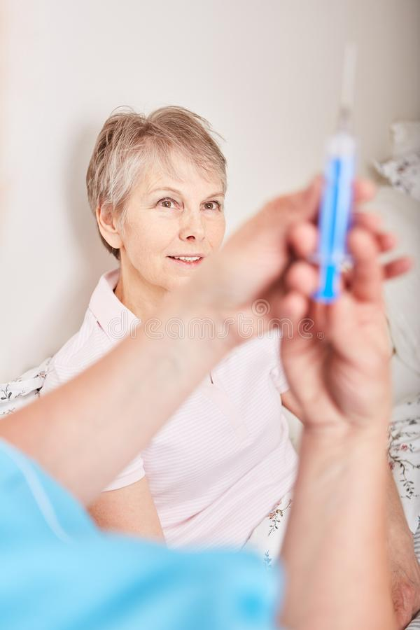 Nurse holds syringe while patient observes royalty free stock photography