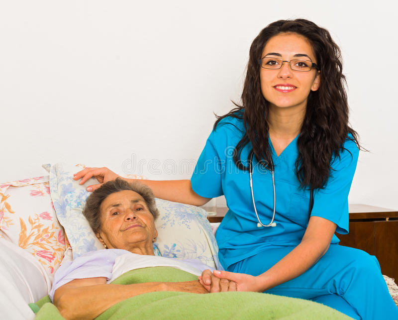 Nurse at Home. Kind nurse women with senior patient at home stock image