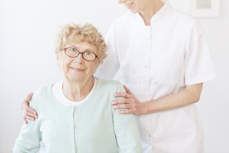 Nurse hugs smiling elderly lady. Young nurse hugs smiling elderly lady in glasses and mint sweater in nursing house royalty free stock image