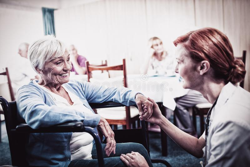 Nurse interacting with a senior woman in wheelchair royalty free stock photography