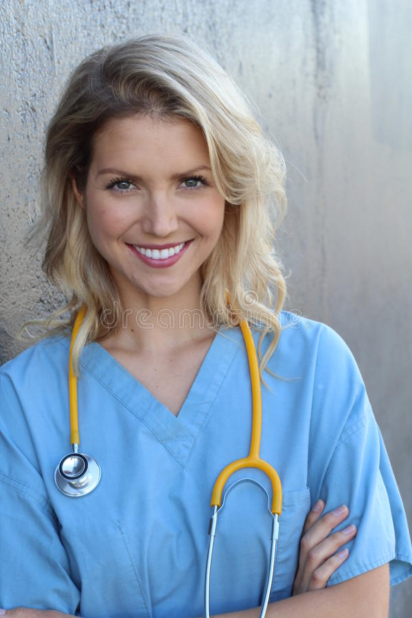 Nurse with long blonde hair and a stethoscope in a uniform smiling at the camera stock photos