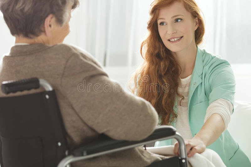 Nurse looking at elder woman. Supportive young nurse looking at elder woman royalty free stock photography