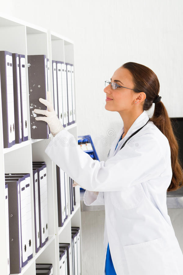 Nurse looking files. Young female nurse looking for patient's files in office stock image