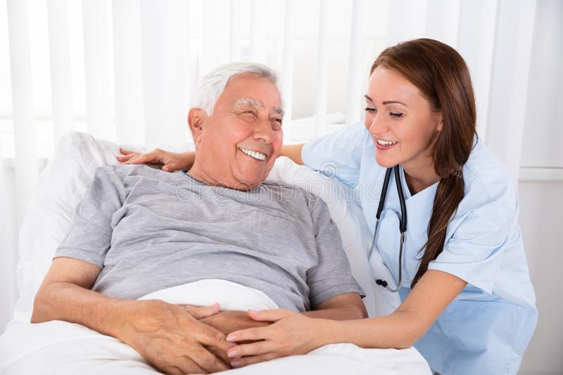 Nurse Looking At Happy Male Patient In Clinic. Nurse Looking At Happy Male Patient Lying On Bed In Clinic royalty free stock photo