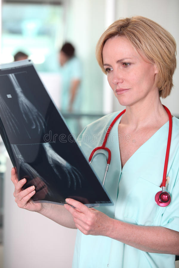 Nurse looking at X-ray. Nurse looking at an X-ray image royalty free stock photography