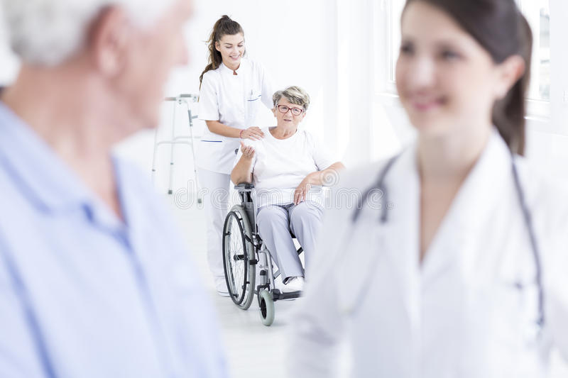 This nurse makes her happy. Shot of a young nurse standing behind a women sitting in the wheelchair royalty free stock images
