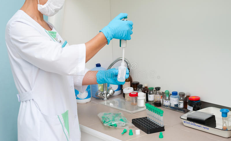 Nurse makes laboratory analysis. A nurse makes an analysis at a clinic laboratory royalty free stock images
