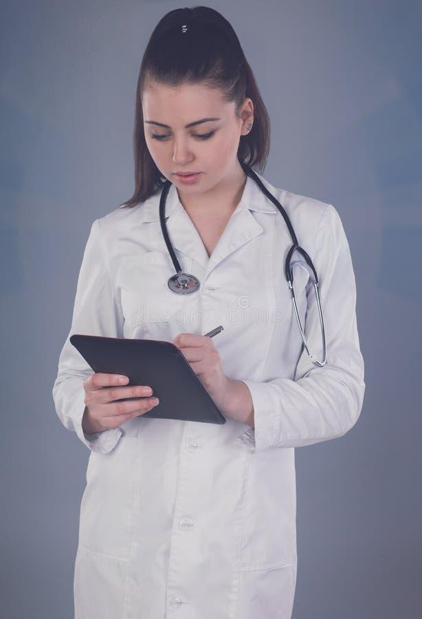 Nurse makes notes. Beautiful nurse with stethoscope is writting something against of grey background royalty free stock photo