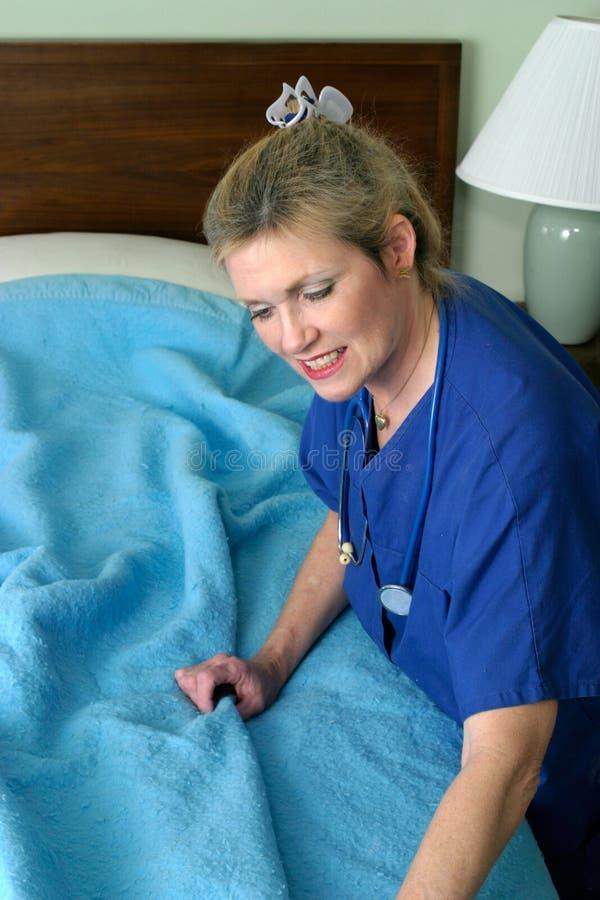 Nurse making hospital bed. Photo of nurse with stethoscope making hospital bed with blue blanket stock photography