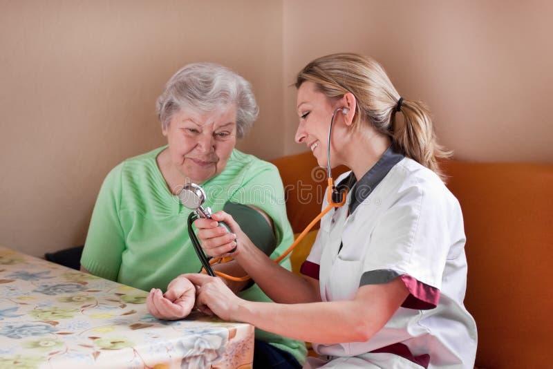 Nurse measures blood pressure of an elderly woman stock images