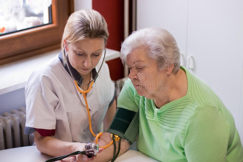 Nurse measures blood pressure of an patient. Nurse makes home visits and measured blood pressure royalty free stock image