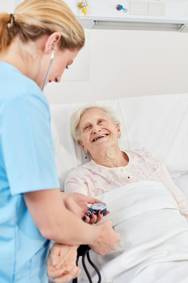 Nurse measures blood pressure of a senior woman. Nurse measures the blood pressure of a happy senior women in the hospital bed royalty free stock photo
