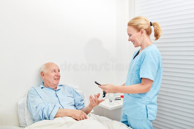 Nurse measures blood sugar in a senior royalty free stock images