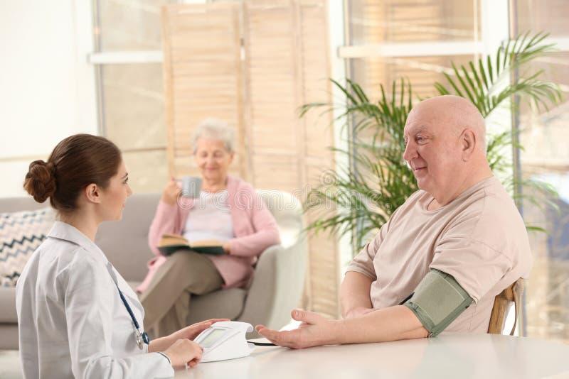 Nurse measuring blood pressure of elderly man. Assisting senior generation royalty free stock photo