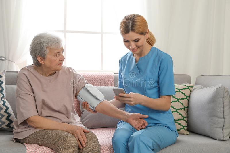 Nurse measuring blood  of elderly woman indoors. Assisting senior people stock image