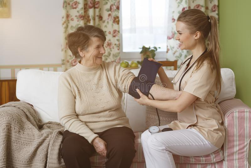 Nurse measuring blood pressure. Happy nurse measuring blood pressure of a senior women in living room stock image