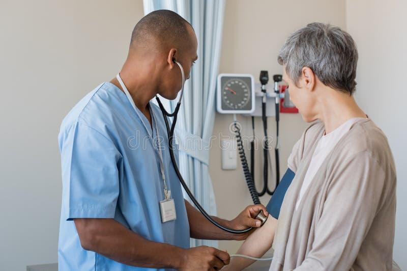 Nurse measuring blood pressure stock photos