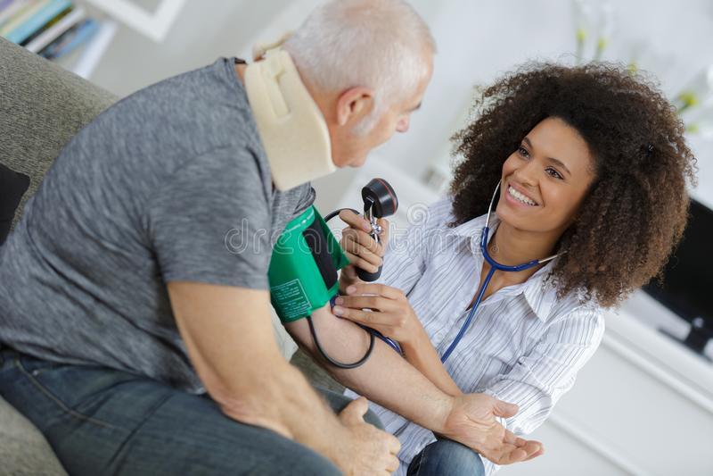 Nurse measuring blood pressure senior at home stock images