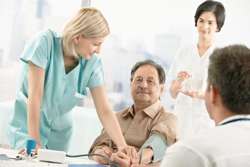 Nurse measuring patient blood pressure stock images