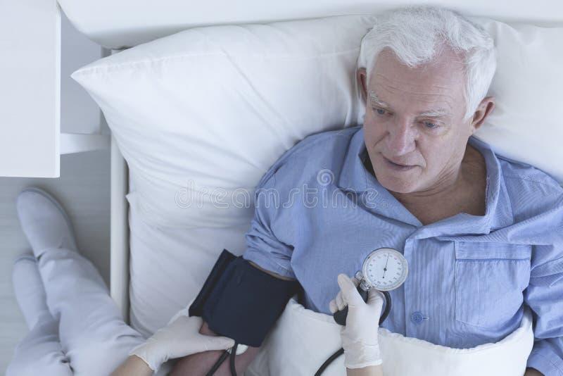 Nurse measuring patient's blood pressure stock photography