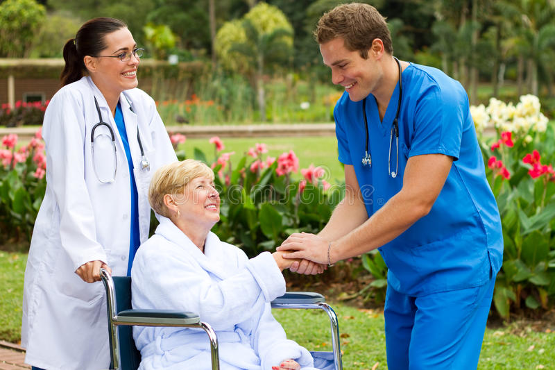 Nurse meet patient. Friendly male nurse meet happy senior patient in hospital backyard