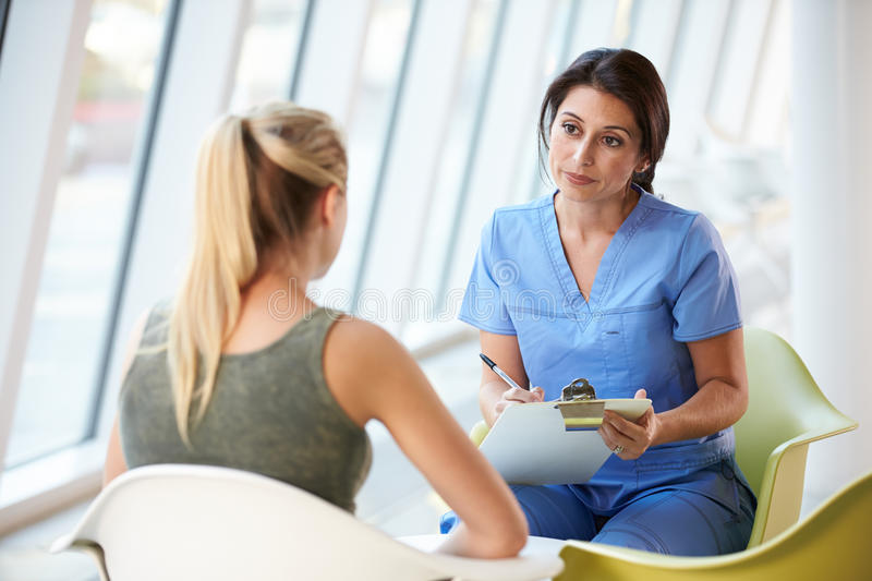 Nurse Meeting With Teenage Girl In Modern Hospital. Sitting Down stock photo