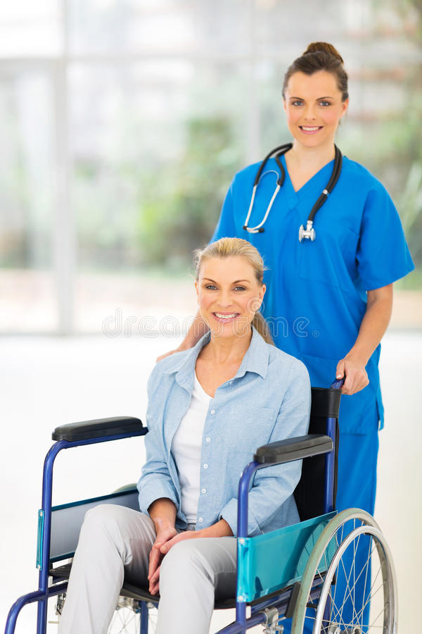 Nurse middle aged patient. Beautiful young nurse pushing middle aged patient on wheelchair royalty free stock photography