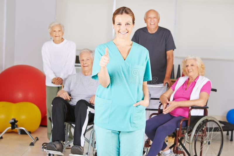 Nurse in nursing home holds thumbs up royalty free stock photo