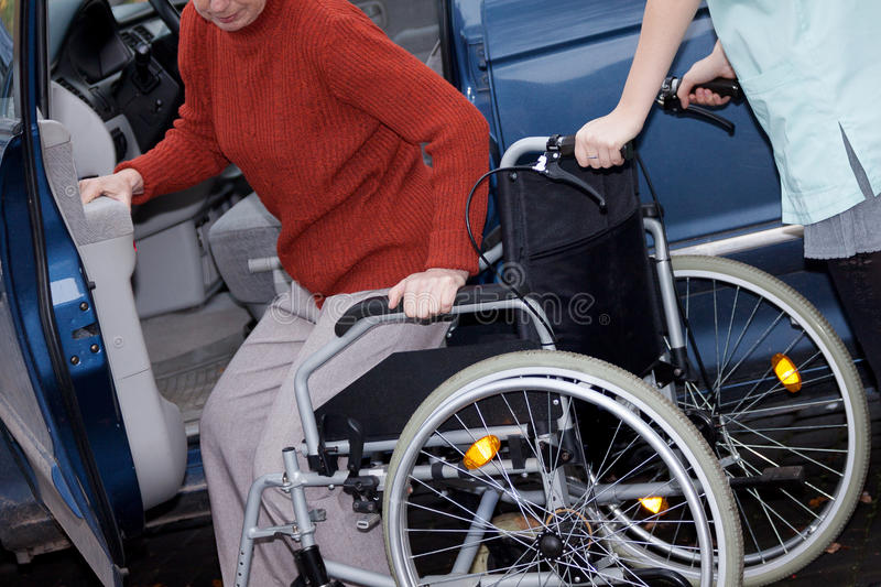Nurse offering a wheelchair. To elder lady who has just arrived to hospital stock photos