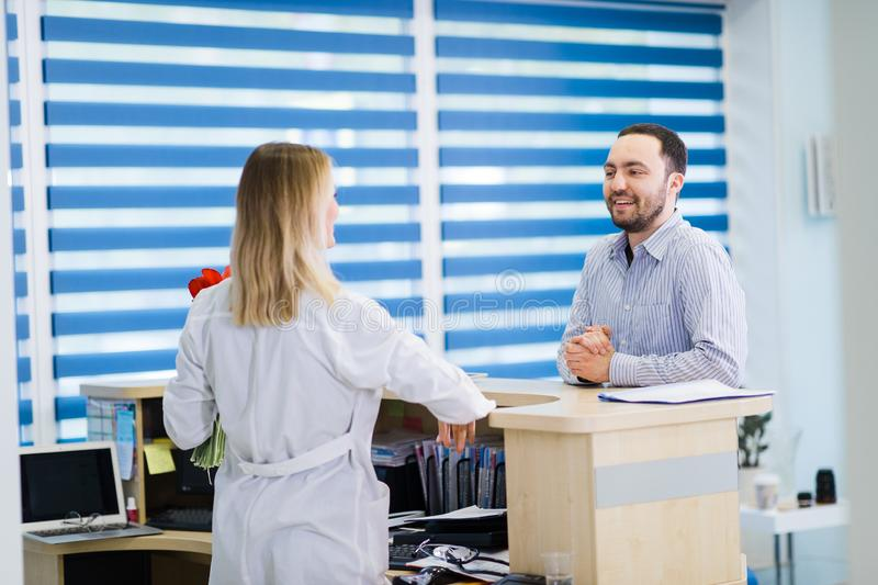 Nurse and patient conversing at reception desk in hospital.  stock photo