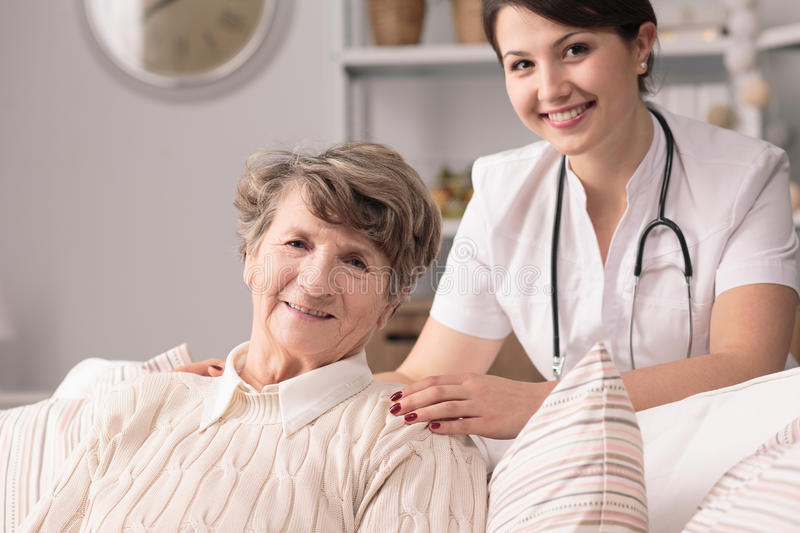 Nurse and patient. Young pretty nurse and her nice senior patient stock image