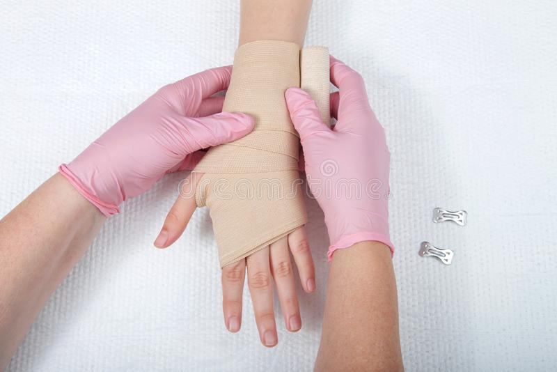 Nurse with pink gloves wrapping young girls hand with ace bandage. Young female hands wearing pink gloves wrapping elastic ace bandage on young hand and wrist stock photos