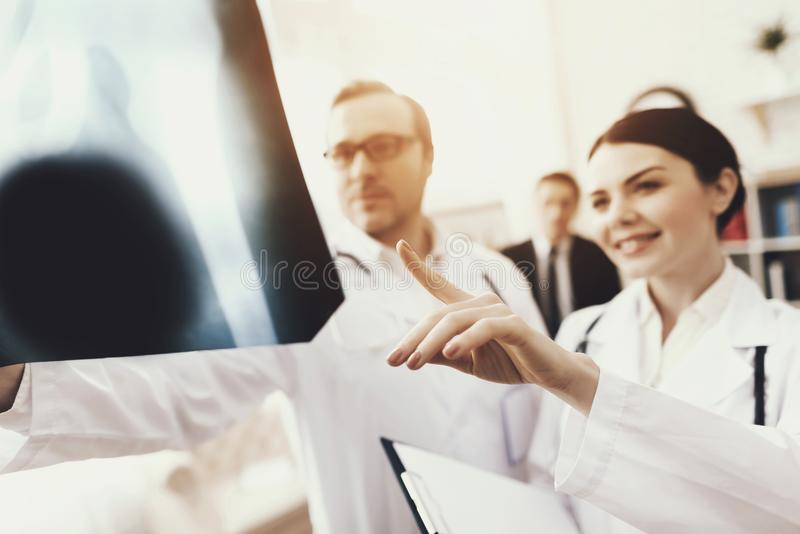 Nurse points to x-ray of pelvic bones that doctor is holding. Blurred. X-ray of pelvic bones. royalty free stock images