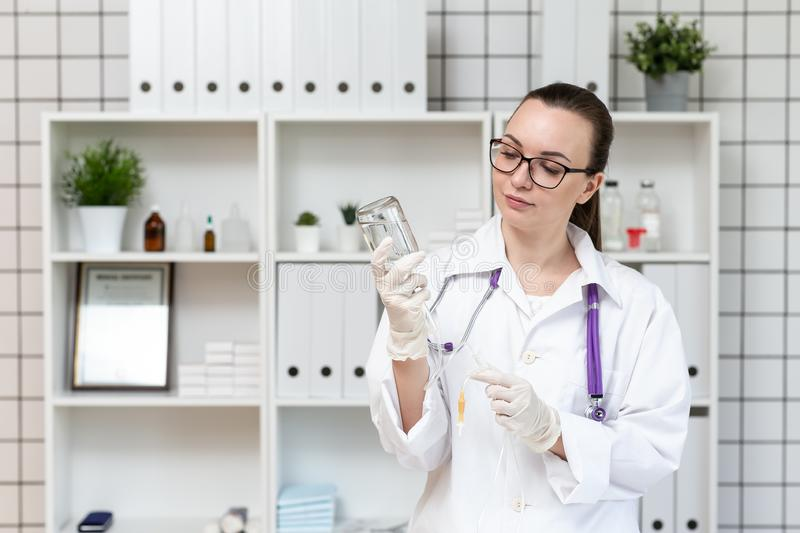 The nurse prepares a dropper with a solution of medicine. stock photography